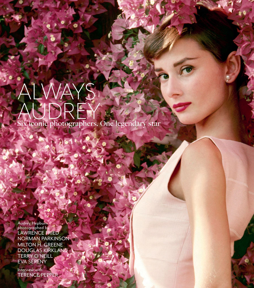 Photograph of Audrey Hepburn in pink dress looking at camera leaning on wall of pink bougainvillea flowers, on front cover of Always Audrey by ACC Art Books