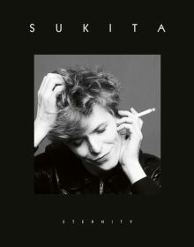 A black and white photo of David Bowie, head tilted down, wry grin and cigarette in hand with title Sukita above and Eternity below.