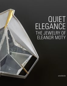 A close-up photograph of an angled, clear gem shaped with metal and gold on a black background and thin white font Quiet Elegance